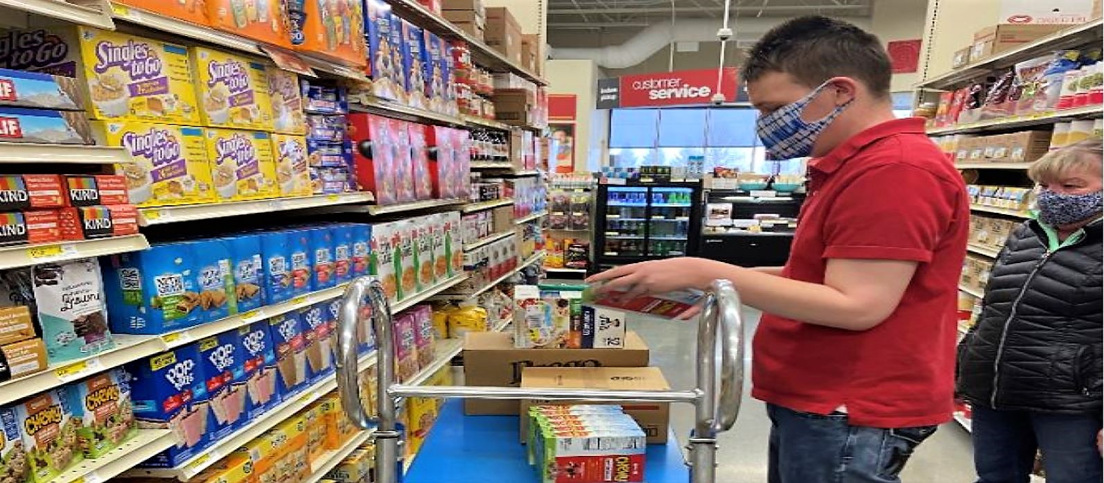 An LCS participant is stocking shelves at GFS for an internship